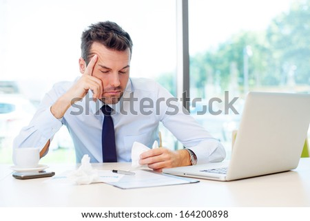 Sick man with cold virus at work - stock photo