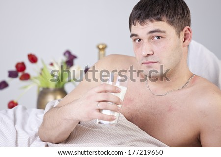 Sick man with glass milk on bed - stock photo