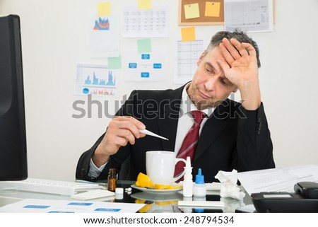 Sick Mature Businessman Suffering From Fever Looking At Thermometer - stock photo