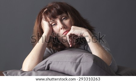 sick mature woman resting her face and hands laying down on cushions for comfort while having health care problems