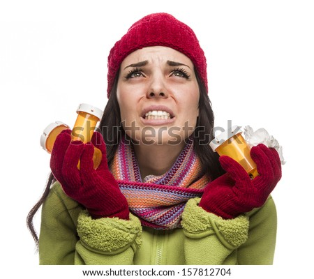 Sick Mixed Race Woman Wearing Winter Hat and Gloves Blowing Her Sore Nose and Holding Empty Medicine Bottle Isolated on White.  - stock photo