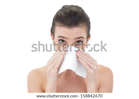 Sick natural brown haired model sneezing in a tissue on white background