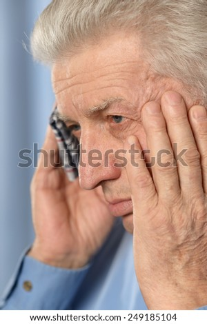Sick old man standing on brown background