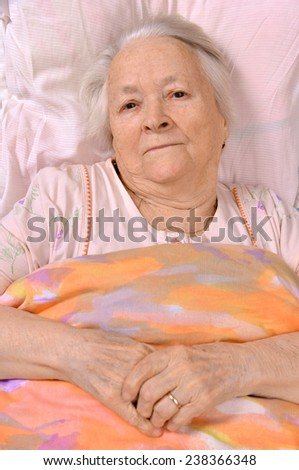 Sick old woman lying at bed - stock photo