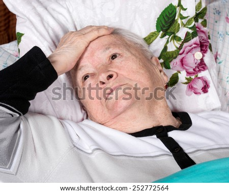 Sick old woman lying in bed - stock photo