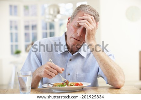 Sick older man trying to eat - stock photo