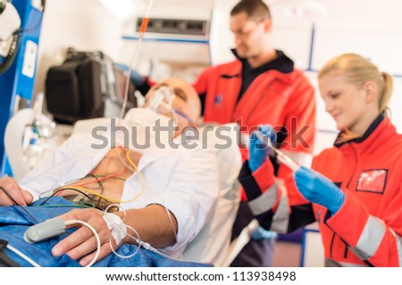 Sick patient with paramedics in ambulance treatment aid emergency work - stock photo