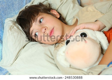 sick preteen boy in bed with sheep toy