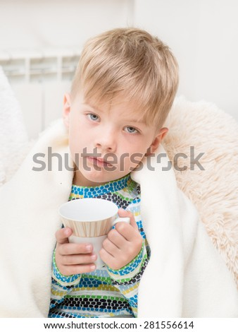sick sad boy with a cup in his hand sitting on the bed wrapped in a blanket - stock photo