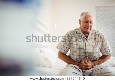 Sick senior man suffering from stomach ache holding his stomach in bedroom - stock photo