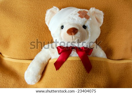 sick teddy bear in bed waiting for the doctor - stock photo