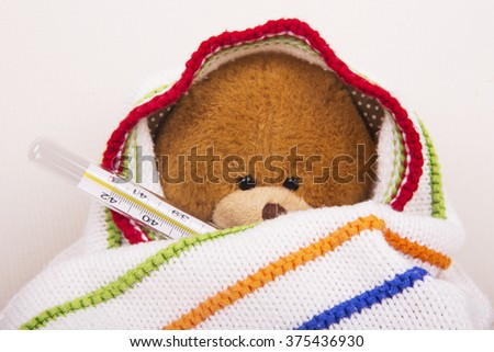 sick teddy bear with thermometer - stock photo