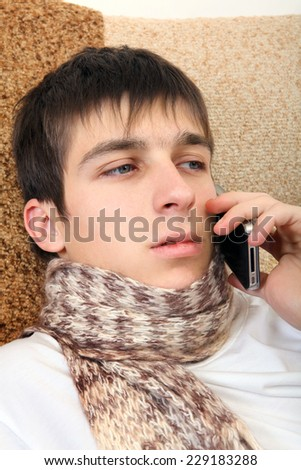 Sick Teenager with Cellphone on the Sofa at the Home - stock photo