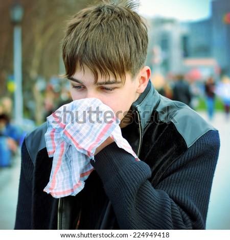 Sick Teenager with Handkerchief on the City Street - stock photo