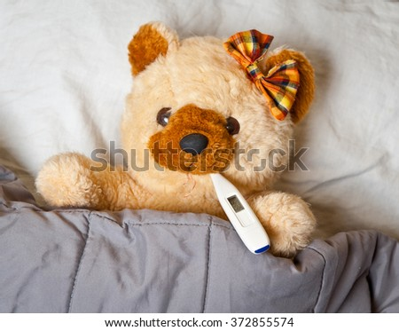 sick toy bear in bed with thermometer in mouth - stock photo