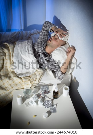 sick wasted man lying in bed suffering cold , headache and winter flu virus having lots of medicine , pills and tablets in health care concept  - stock photo