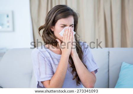 Sick woman blowing her nose at home in the living room
