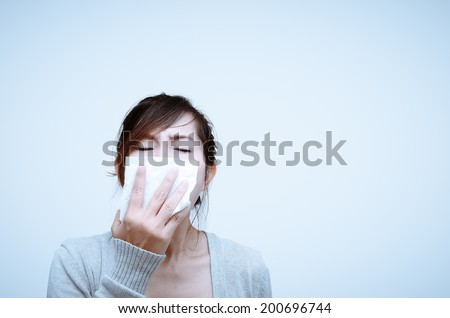 Sick woman blowing her nose isolated. - stock photo