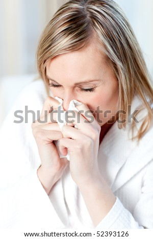 Sick woman blowing sitting on a sofa - stock photo