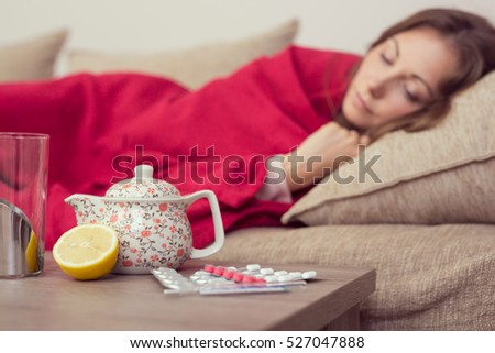 Sick woman covered with a blanket lying in bed with high fever and a flu, resting. Teapot, pills and lemon on the table, focus on the teapot