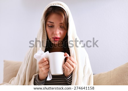 Sick woman covered with blanket holding cup of tea sitting on sofa couch - stock photo