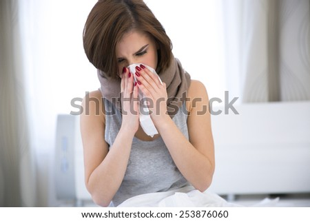 Sick Woman. flu. woman caught cold. sneezing into tissue - stock photo