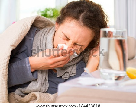 Sick Woman. Flu. Woman Caught Cold. Sneezing into Tissue. Headache. Virus. Medicines  - stock photo