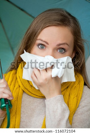 Sick woman holding umbrella and blowing her nose - stock photo
