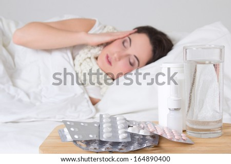 sick woman in bed and pills on the bedside table