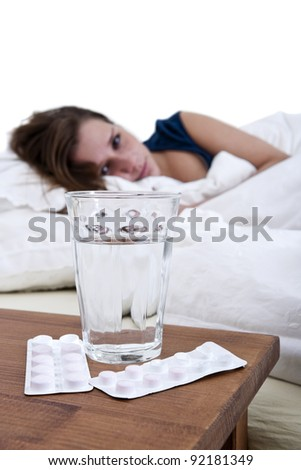 Sick woman in bed, looking at a glass of water, and two blister strips with pills