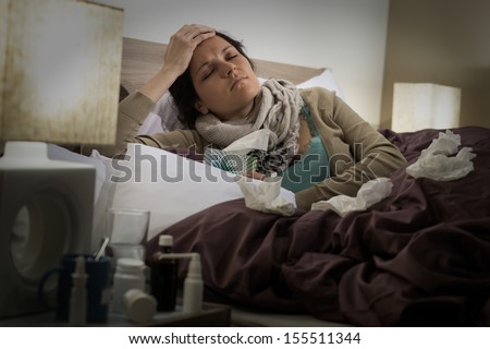 Sick woman in bed suffering from flu headache - stock photo
