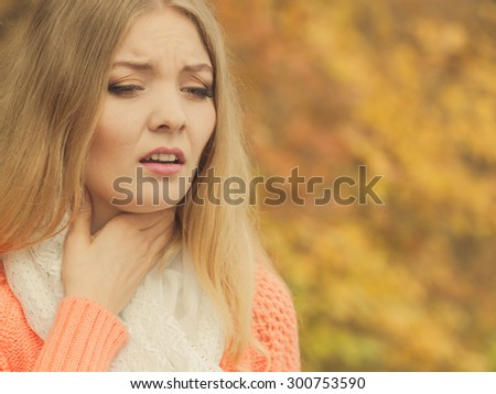 Sick woman in fall autumn park. Ill girl caught cold flu outdoor. Rhinitis or allergy. Health care. - stock photo