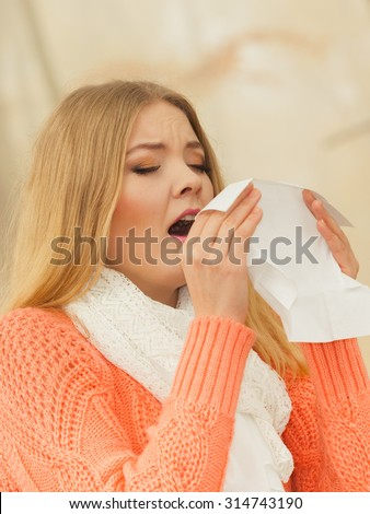 Sick woman in fall autumn park sneezing in tissue. Ill girl caught cold flu outdoor. Rhinitis or allergy. Health care. - stock photo