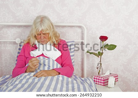 Sick woman in pink pajama with thermometer, tissues and a rose lying in bed with washcloth - stock photo
