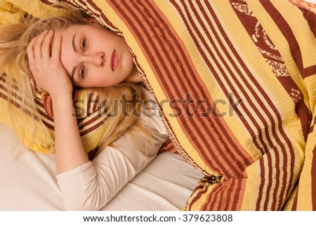 Sick woman lying in bed covered with blanket, feeling ill, has flu, fever and headache. - stock photo