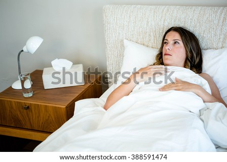 sick woman lying in bed surrounded by tissues and water - stock photo