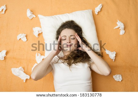 Sick woman lying in bed with cold and flu. She has a headache. - stock photo