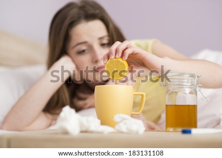 Sick woman lying in bed with high fever. She has cold and flu. She is drinking tea with honey and lemon. - stock photo