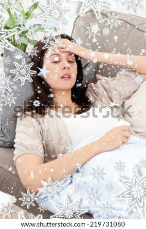 Sick woman lying on the sofa and touching her forehead against snow falling - stock photo