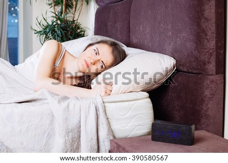 sick woman on bed in bedroom massaging her head to relieve pain or stress