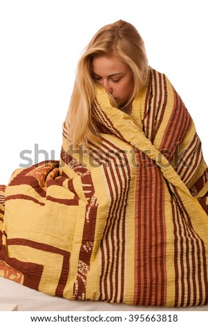 Sick woman sitting on bad wrapped in a blanket feeling ill, has flu and fever. - stock photo