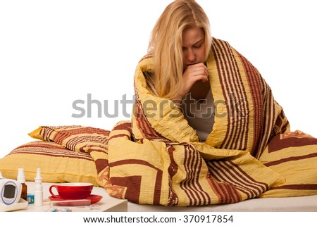 Sick woman sitting on bad wrapped in a blanket feeling ill, has flu, fever, cold and cough. - stock photo