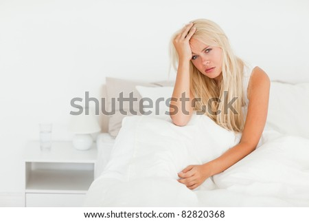 Sick woman sitting on her bed while waking up