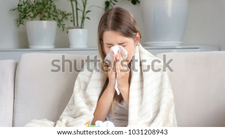 Sick woman sneezing in paper tissue on sofa