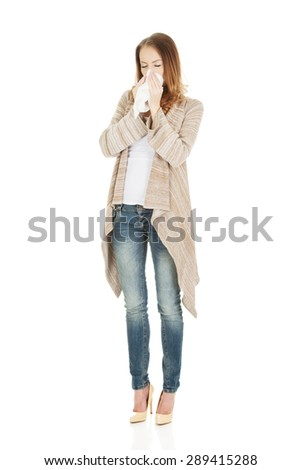 Sick woman sneezing into tissue. - stock photo