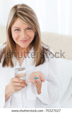 Sick woman taking her pills at home - stock photo