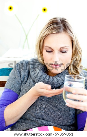 Sick woman taking pills holding a glass of water sitting on a sofa