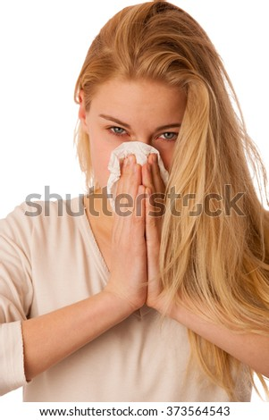 Sick woman with flu and fever blowing nose in tissue isolated over white background.