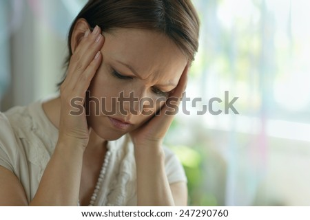Sick woman with headache at home