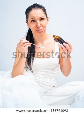 Sick woman with influenza in bed, holding a cough syrup bottle